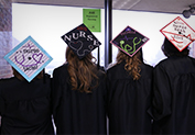 four students showing the back of their graduation caps