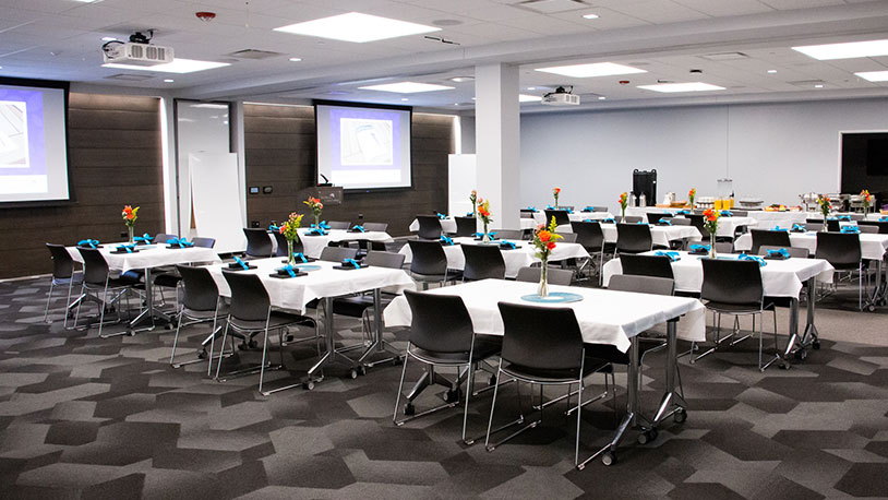 large conference room with projector and dining tables for event