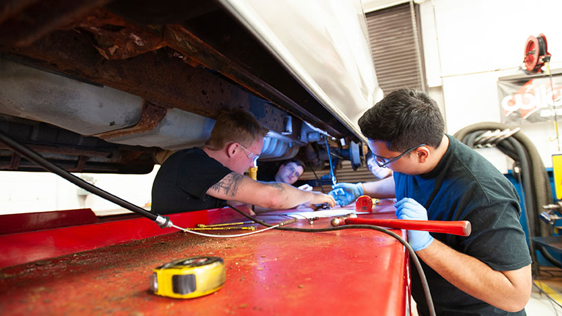automotive students working under hood of car