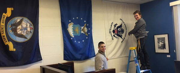 photo of putting flags up on wall in Veterans' Service Center